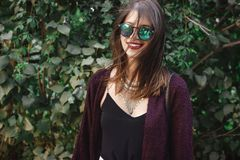 太阳镜的微笑在晴朗的庭院里的愉快的boho女孩画象  时髦的摆在绿色背景的行家无忧无虑的女孩  免版税库存图片