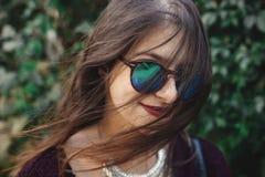太阳镜的微笑在晴朗的庭院里的愉快的boho女孩画象  时髦的摆在绿色背景的行家无忧无虑的女孩  图库摄影