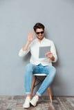 太阳镜的微笑的人使用片剂和有电视电话会议 免版税图库摄影