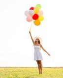 太阳镜的微笑的少妇有气球的 免版税图库摄影