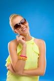 太阳镜的微笑的时尚妇女在蓝色背景。 库存图片