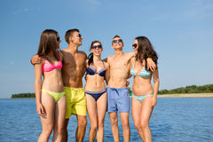 太阳镜的微笑的朋友在夏天海滩 免版税图库摄影