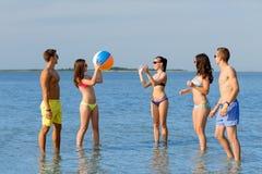 太阳镜的微笑的朋友在夏天海滩 免版税库存图片