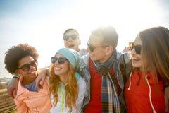 太阳镜的微笑的朋友笑在街道上的 免版税库存图片