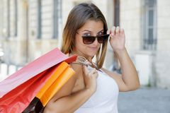 太阳镜的快乐的年轻女人有袋子的 免版税库存照片