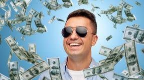太阳镜的愉快的人有落的美元金钱的 免版税库存图片