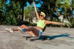太阳镜的愉快的可爱的少妇坐滑板在棕榈附近在公园 免版税库存照片