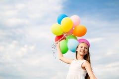 太阳镜的愉快的女孩有气球的 库存图片