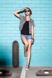太阳镜的愉快的女孩有滑板的获得乐趣为 免版税库存图片
