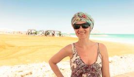 太阳镜的愉快的妇女在海滩死海 库存照片