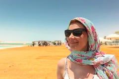 太阳镜的愉快的妇女在海滩死海 免版税库存图片