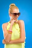 太阳镜的愉快的妇女在蓝色背景。 库存照片