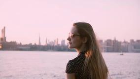 太阳镜的愉快的年轻白种人女孩有吹在风观看的日落的头发的在城市河海滩慢动作 股票视频