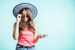 太阳镜的愉快的微笑的妇女和调查照相机的帽子,握她的在智能手机的手 免版税图库摄影