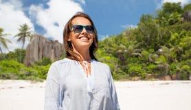 太阳镜的愉快的微笑的妇女在海滩 免版税库存照片