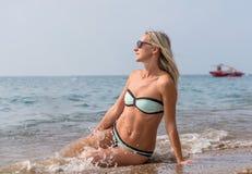 黑太阳镜的愉快的微笑的少妇在天时间的海 正面人的情感,感觉,喜悦 春天和summe 免版税库存照片