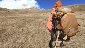 太阳镜的愉快的旅客女孩摄影师有照相机和背包的在背景去上升积雪覆盖 股票视频