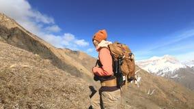 太阳镜的愉快的旅客女孩摄影师有照相机和背包的在背景去上升积雪覆盖 股票录像