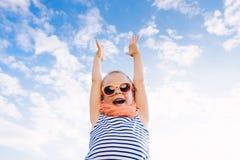 太阳镜的愉快的漂亮的孩子女孩用开放手反对 免版税库存图片