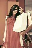 太阳镜的愉快的年轻时尚妇女有购物袋的 免版税库存照片