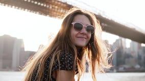 太阳镜的慢动作愉快的女孩有惊人的金黄头发的吹在风微笑对照相机的在布鲁克林大桥 股票录像
