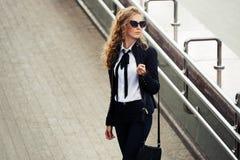 太阳镜的时装业妇女走在城市街道上的 免版税库存图片