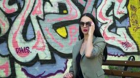 太阳镜的时髦的妇女坐长凳对有街道街道画的墙壁 股票视频