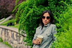 太阳镜的深色的女性在夏天公园喝咖啡 图库摄影