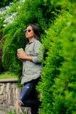 太阳镜的深色的女性在夏天公园喝咖啡 免版税库存照片
