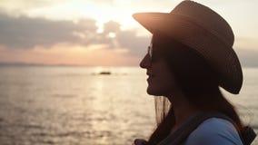 太阳镜的特写镜头微笑的旅行妇女投入在帽子敬佩令人惊讶的海风景的在日落 股票视频