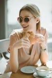 太阳镜的白种人女孩用在咖啡馆的新月形面包,有午餐概念 免版税库存图片