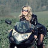 太阳镜的白肤金发的妇女在体育摩托车 免版税库存照片