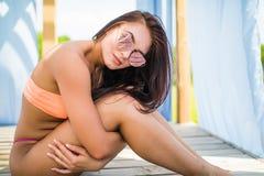 太阳镜的秀丽妇女在有她的腿在休息室床上放松在水池的性感的身体拥抱的比基尼泳装佩带 沿着砖帽子对集会池休息的闪耀的秸杆夏天太阳镜 免版税图库摄影