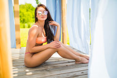 太阳镜的秀丽妇女在有性感的身体的比基尼泳装在休息室床上佩带放松在水池 沿着砖帽子对集会池休息的闪耀的秸杆夏天太阳镜 免版税库存照片