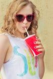 太阳镜的美丽的女孩在夏天温暖的天饮用的焦炭通过与红色玻璃的秸杆 库存图片