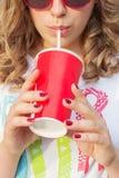 太阳镜的美丽的女孩在夏天温暖的天饮用的焦炭通过与红色玻璃的秸杆 免版税库存照片