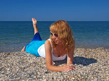 太阳镜的美丽的女孩在海滩 免版税库存照片
