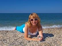 太阳镜的美丽的女孩在海滩 库存照片