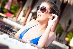 太阳镜的美丽的女孩在豪华水池 库存照片