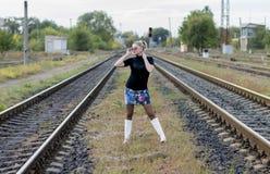 太阳镜的美丽的妇女在两条铁路轨道之间 库存图片