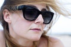 太阳镜的美丽的妇女在海滩 免版税库存照片