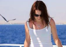 太阳镜的美丽的妇女在游艇 免版税库存图片