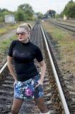 太阳镜的美丽的妇女在铁路路轨 库存图片