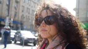 太阳镜的美丽的少妇在城市 股票录像