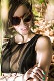 太阳镜的美丽的年轻女人微笑对照相机的下 图库摄影