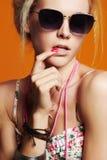 太阳镜的美丽的性感的女孩 20秀丽世纪回顾展复核s妇女xx 橙色背景 库存照片