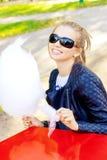 太阳镜的美丽的愉快的微笑的女孩吃棉花糖的在一张桌上在公园在一个晴天 免版税库存照片
