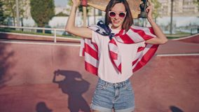 太阳镜的美丽的愉快的微笑的深色的行家女孩在美国国旗和举行包裹的冰鞋公园 影视素材