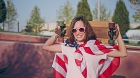 太阳镜的美丽的愉快的微笑的深色的行家女孩在美国国旗和举行包裹的冰鞋公园 股票视频