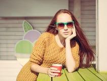 太阳镜的美丽的红发女孩夏天室外咖啡馆桌的 免版税库存图片